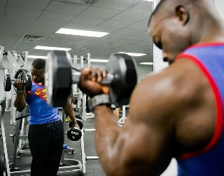 man doing bicep curl in a gym